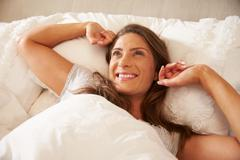 Woman Waking Up And Stretching In Bed At Home Stock Photos