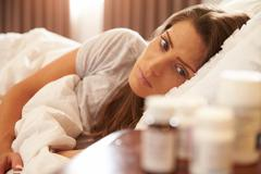 Unhappy Woman Looking At Medication On Bedside Table Stock Photos