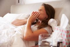 Woman Suffering From Cold Lying In Bed With Tissue Stock Photos