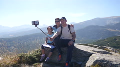 Stock Video Footage of Tourists happy family in mountains making selfie via smart phone on a stick