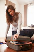 Woman Packing For Vacation Trying To Close Full Suitcase Stock Photos