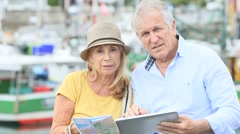 Senior couple looking at map while visiting city - stock footage