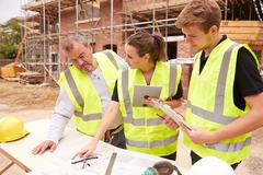 Builder On Building Site Discussing Work With Apprentices Stock Photos