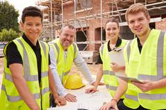 Portrait Of Builder On Building Site With Apprentices - stock photo