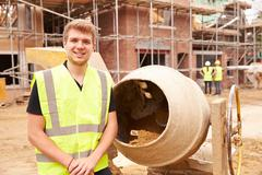 Portrait Of Worker On Building Site Mixing Cement Stock Photos