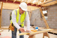 Carpenter Cutting House Roof Supports On Building Site Stock Photos
