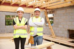 Carpenter With Female Apprentice Working On Building Site Stock Photos