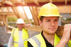 Builder And Apprentice Carrying Wood On Construction Site - stock photo