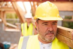 Builder And Apprentice Carrying Wood On Construction Site Stock Photos