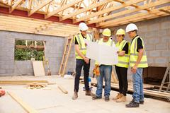 Builder On Building Site Looking At Plans With Apprentices Stock Photos