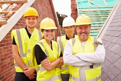 Portrait Of Builder On Building Site With Apprentices Stock Photos