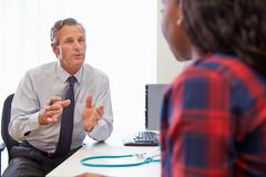 Female Patient Having Consultation With Doctor In Office Stock Photos
