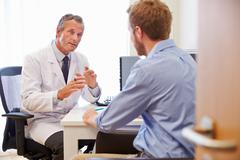 Male Patient Having Consultation With Doctor In Office Stock Photos