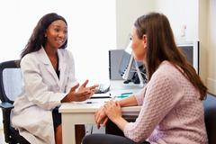 Patient Having Consultation With Female Doctor In Office - stock photo