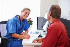 Senior Patient Having Consultation With Nurse In Office Stock Photos