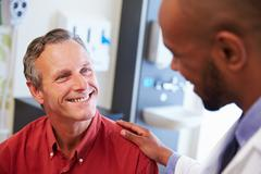 Male Patient Being Reassured By Doctor In Hospital Room Stock Photos