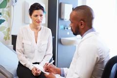 Female Patient And Doctor Have Consultation In Hospital Room Stock Photos