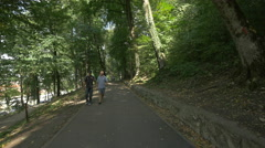 Tourists walking on an alley inside the forest of Tampa hill, Brasov Stock Footage