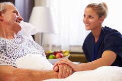 Nurse Talking To Senior Male Patient In Hospital Bed Stock Photos