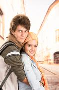 Stock Photo of Young couple embracing posing in city environment showing love and affection for