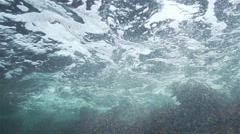 underwater turbulence with oxygen bubbles from broken wave in rock - stock footage