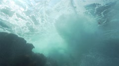 Underwater wave breaks in the rock and form turbulence with bubbles Stock Footage