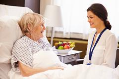 Doctor Talking To Senior Female Patient In Hospital Bed Stock Photos