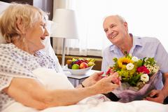 Husband Visiting Senior Wife In Hospital With Flowers Stock Photos