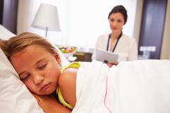 Doctor Observing Sleeping Child Patient In Hospital Bed Stock Photos