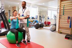 Female Patient Working With Physiotherapist In Hospital Stock Photos