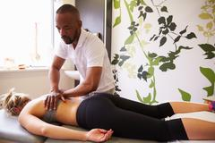 Physiotherapist Giving Female Patient Massage In Hospital Stock Photos