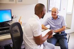 Senior Male Patient Working With Physiotherapist In Hospital Stock Photos