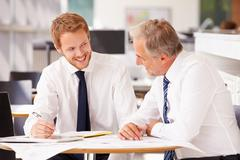 Two corporate business colleagues working together in office Stock Photos