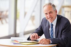 Portrait of smiling senior corporate businessman, waist up Stock Photos