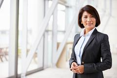 Portrait of smiling Asian businesswoman, standing - stock photo
