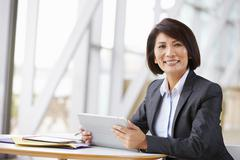 Asian businesswoman with digital tablet,  smiling to camera Stock Photos