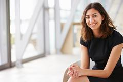 Portrait of young mixed race Asian businesswoman sitting Stock Photos