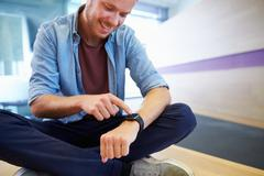 Casually dressed man sits cross legged pointing at his watch Stock Photos