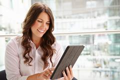 Young businesswoman using tablet computer, waist up - stock photo