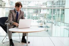 Corporate businessman using laptop computer, full length Stock Photos