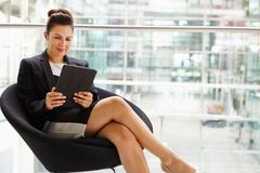 Businesswoman using tablet computer, three quarter length - stock photo