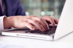 Close up of businessman?s hands using the keypad of a laptop - stock photo