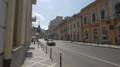 Driving cars on Muresenilor street next to Council Square, Brasov Stock Footage