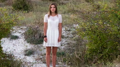 Young woman standing in a lacy white dress on background of green plants Stock Footage