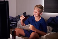 Teenage Boy Addicted To Video Gaming At Home Stock Photos
