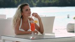 Beautiful girl drink cocktail in cafe near the river Stock Footage