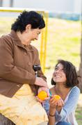 Grandmother granddaughter quality time outdoors holding an orange - stock photo