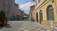 Women talking on Republicii street, near a food carriage and Otter store, Brasov Stock Footage