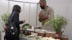 Herbalist vendor sell natural perfume, aroma and soaps in annual fair. 4K Stock Footage