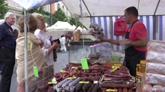 Butcher vendor man sell smoked meat for elder woman in city market. 4K Stock Footage